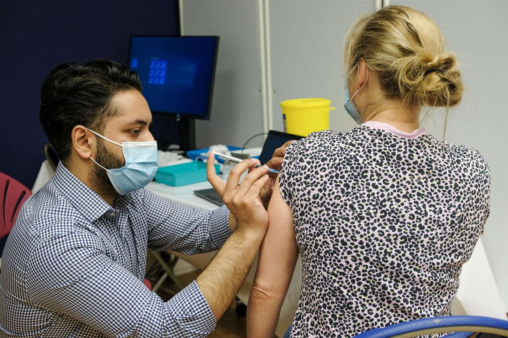 A vaccination agent injects a patient.